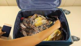 La muchacha está embalando la maleta con las porciones de dinero para el viaje del día de fiesta o de fin de semana almacen de video