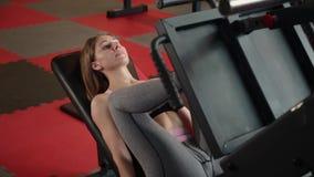 La muchacha está en el gimnasio que hace la máquina de la prensa de la pierna almacen de metraje de vídeo