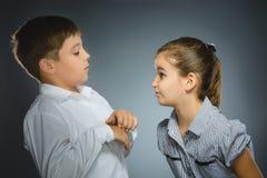 La muchacha está enojada en el muchacho asustado en fondo gris Concepto de la comunicación fotografía de archivo