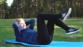 La muchacha está entrenando en el parque en el césped metrajes