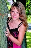 La muchacha está escogiendo detrás del árbol fotografía de archivo libre de regalías