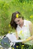 La muchacha está escribiendo en un cuaderno en un prado verde en el parque Imagen de archivo
