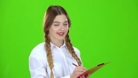 La muchacha está escribiendo en una tableta blanca Pantalla verde almacen de metraje de vídeo