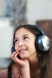 La muchacha está escuchando la música Foto de archivo
