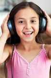 La muchacha está escuchando la música Fotografía de archivo
