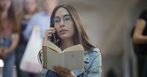 La muchacha está esperando la parada del metro - habla en el teléfono y lee el libro almacen de metraje de vídeo