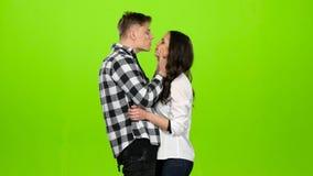 La muchacha está esperando a su individuo querido, él viene y suavemente los besos Pantalla verde almacen de metraje de vídeo