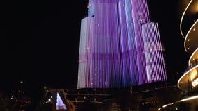 La muchacha está filmando la torre de Burj Khalifa en la noche almacen de metraje de vídeo