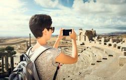 La muchacha está fotografiando las ruinas del teléfono Viaje Túnez, Dougga Imágenes de archivo libres de regalías