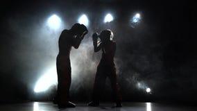 La muchacha está golpeando a un individuo con el pie con su entrenamiento kickboxing Luz de detrás Fume el fondo Silueta metrajes