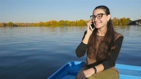 La muchacha está hablando en el teléfono mientras que se sienta en un barco en el agua Sonrisa bonita Día asoleado Cámara lenta almacen de metraje de vídeo