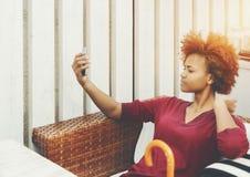 La muchacha está haciendo el selfie mientras que se sienta en barra de la calle Imagenes de archivo
