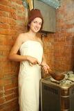 La muchacha está haciendo el vapor en la sauna Imágenes de archivo libres de regalías