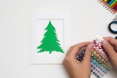 La muchacha está haciendo la tarjeta de Navidad Foto de archivo libre de regalías