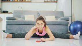 La muchacha está haciendo la preparación mientras que hace ejercicios del teléfono