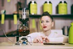 La muchacha está haciendo té en un café Imagenes de archivo