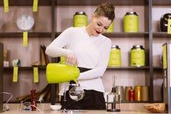 La muchacha está haciendo té en un café Fotos de archivo