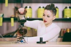 La muchacha está haciendo té en un café Fotos de archivo libres de regalías