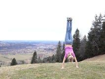 La muchacha está haciendo una posición del pino en una montaña Foto de archivo libre de regalías