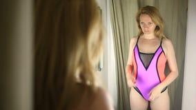 La muchacha está intentando en un traje de baño en el vestuario de una ropa interior del ` s de la mujer almacen de video