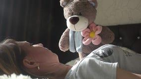 La muchacha está jugando con un oso de peluche y está sonriendo mientras que se sienta en su cama en casa almacen de metraje de vídeo