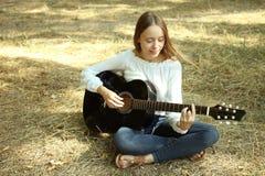 La muchacha está jugando en una guitarra acústica Imagen de archivo