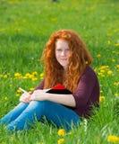 La muchacha está leyendo en prado de la primavera Fotos de archivo