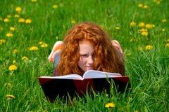 La muchacha está leyendo en prado de la primavera Fotografía de archivo