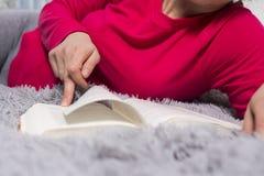 La muchacha está leyendo Manos y primer del libro El concepto de lectura Una mujer joven está leyendo una novela Lea un gran libr Foto de archivo