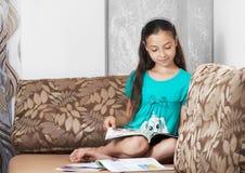 La muchacha está leyendo un compartimiento Imagenes de archivo