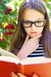 La muchacha está leyendo un libro Fotos de archivo