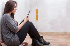 La muchacha está leyendo un libro con un lector del eBook Imagen de archivo libre de regalías
