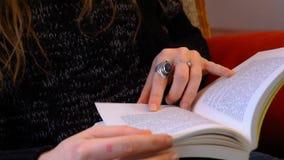 La muchacha está leyendo un libro en una sala de estar almacen de video