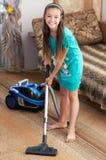 La muchacha está limpiando la alfombra con la aspiradora fotografía de archivo libre de regalías