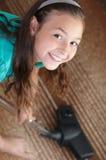 La muchacha está limpiando la alfombra con la aspiradora imágenes de archivo libres de regalías