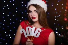 La muchacha está llevando a cabo los números de papel 2016, tiempo de la Navidad Fotos de archivo libres de regalías