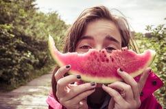 La muchacha está llevando a cabo una rebanada mordida de melón Fotos de archivo