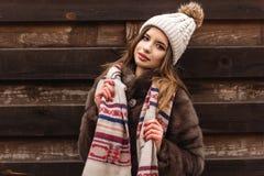 La muchacha está llevando el sombrero y la bufanda cerca de la pared de madera Foto de archivo