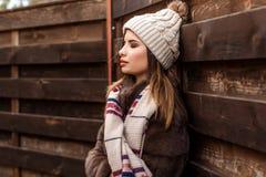 La muchacha está llevando el sombrero y la bufanda cerca de la pared de madera Imagen de archivo