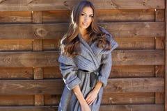 La muchacha está llevando la ropa hecha punto cerca de la pared de madera Fotografía de archivo libre de regalías
