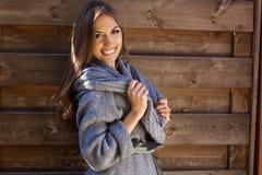 La muchacha está llevando la ropa hecha punto cerca de la pared de madera Foto de archivo libre de regalías
