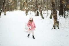 La muchacha está llevando un trineo con las cajas de regalo Foto de archivo