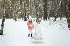La muchacha está llevando un trineo con las cajas de regalo Fotos de archivo libres de regalías