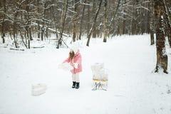 La muchacha está llevando un trineo con las cajas de regalo Imágenes de archivo libres de regalías