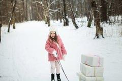 La muchacha está llevando un trineo con las cajas de regalo Foto de archivo libre de regalías