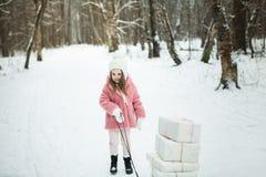 La muchacha está llevando un trineo con las cajas de regalo Imagen de archivo