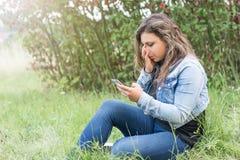 La muchacha está llorando mirando su teléfono elegante Fotos de archivo