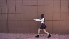 La muchacha está luchando con la espada Entrenamiento de la persona para la lucha importante en la cámara lenta metrajes