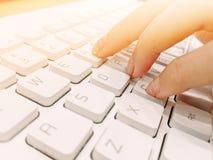 La muchacha está mecanografiando un documento en un teclado blanco imagen de archivo