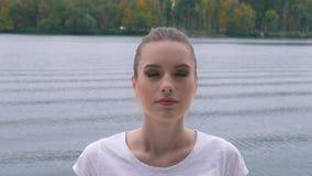La muchacha está meditando cerca del lago almacen de metraje de vídeo